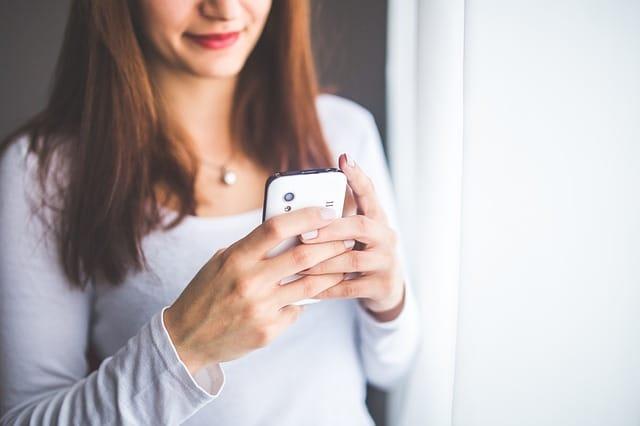 Frau schreibt eine SMS an ihrem Handy